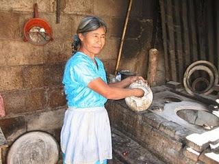 Se ve a una señora de rasgos mayas trabajando con las manos en un taller.